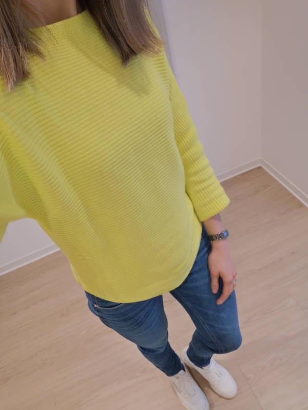 Gelber Pulli mit blauer Jeans und weißen Sneakern